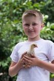 有一只小鸡的男孩 免版税库存图片