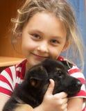 有一只德国牧羊犬小狗的女孩 免版税库存图片