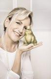 有一只池蛙的相当微笑的老妇人在她的手上 Conce 库存照片