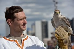 有一只猎鹰的一个人在他的在斯拉夫的全国衣裳的手上在Th 库存照片