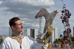 有一只猎鹰的一个人在他的在斯拉夫的全国衣裳的手上在Th 库存图片