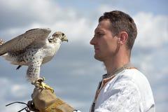 有一只猎鹰的一个人在他的在斯拉夫的全国衣裳的手上在Th 免版税图库摄影