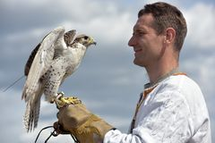 有一只猎鹰的一个人在他的在斯拉夫的全国衣裳的手上在Th 免版税库存图片