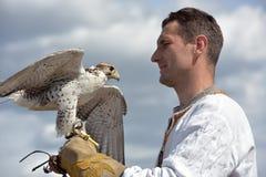 有一只猎鹰的一个人在他的在斯拉夫的全国衣裳的手上在Th 免版税库存照片