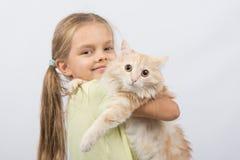 有一只猫的六岁的女孩在她的胳膊 图库摄影