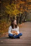 有一只猫的女孩在一个公园在秋天 图库摄影