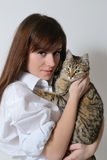 有一只猫的女孩在她的胳膊 免版税库存照片