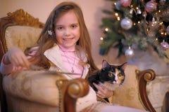 有一只猫的女孩在椅子 库存照片