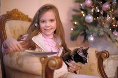 有一只猫的女孩在椅子 免版税库存图片