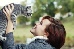 有一只猫的女孩在秋天公园 免版税库存照片
