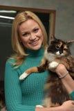 有一只猫的愉快的妇女从风雨棚 库存图片