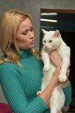 有一只猫的愉快的妇女从风雨棚 免版税库存照片