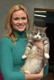 有一只猫的愉快的妇女从风雨棚 库存照片
