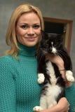 有一只猫的愉快的妇女从风雨棚 免版税库存图片