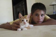 有一只猫的男孩在坏 免版税库存图片