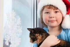 有一只猫的男孩在房子圣诞前夕的冬天窗口附近 库存照片