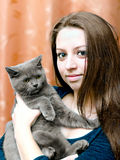 有一只猫的美丽的女孩在现有量 免版税库存图片