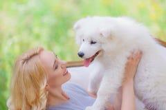有一只白色小狗的美丽的女孩在她的在一个减速火箭的沙发的胳膊在夏天庭院里 免版税库存图片