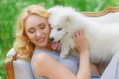 有一只白色小狗的美丽的女孩在她的在一个减速火箭的沙发的胳膊在夏天庭院里 库存照片