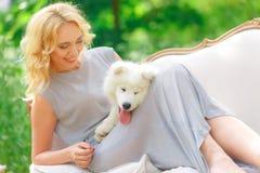 有一只白色小狗的美丽的女孩在她的在一个减速火箭的沙发的胳膊在夏天庭院里 库存图片
