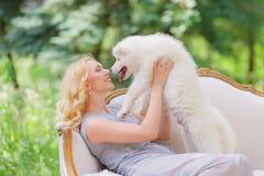 有一只白色小狗的美丽的女孩在她的在一个减速火箭的沙发的胳膊在夏天庭院里 免版税图库摄影