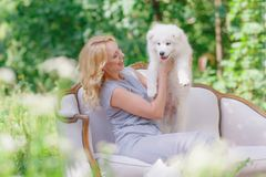 有一只白色小狗的美丽的女孩在她的胳膊和在一个减速火箭的沙发的更旧的白色蓬松狗在一个夏天从事园艺 免版税图库摄影