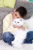有一只白色波斯猫的男孩在家 免版税库存照片
