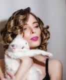 有一只白色蓬松猫的美丽的女孩在她的胳膊 免版税库存图片