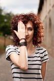 有一只眼睛的红发妇女由她的手关闭了 库存照片