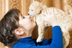 有一只米黄小狗的女孩 免版税库存图片