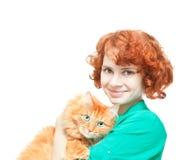 有一只红色猫的卷曲红发女孩 免版税库存图片