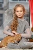 有一只红色猫的女孩 免版税图库摄影