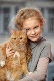 有一只红色猫的女孩 库存照片