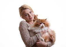 有一只红色猫的好女孩在手上 库存照片