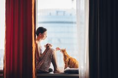 有一只红色猫的少女在家 免版税库存图片