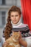 有一只红色猫的青少年的女孩 库存照片