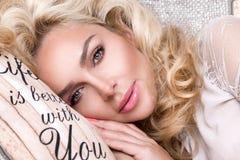 有一只美丽的面孔和惊人的眼睛的,谎言画象美丽的白肤金发的妇女,在典雅的床单睡觉 库存图片