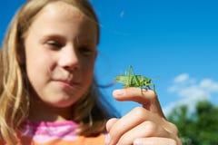 有一只蚂蚱的女孩在手上 免版税库存图片