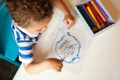 有一只蜡笔的新男孩在他的现有量 图库摄影