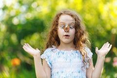 有一只蝴蝶的惊奇的女孩在她的鼻子 库存照片
