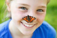 有一只蝴蝶的美丽的女孩在她的鼻子 库存照片