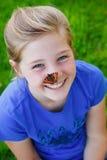 有一只蝴蝶的美丽的女孩在她的鼻子 免版税图库摄影