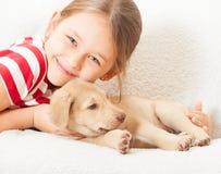 有一只逗人喜爱的小狗的女孩 库存照片