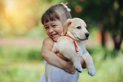 有一只金毛猎犬小狗的小女孩 库存照片