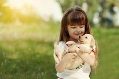 有一只金毛猎犬小狗的小女孩 免版税库存照片