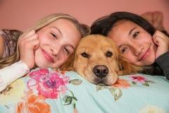 有一只金毛猎犬的两个女孩在家尾随 免版税库存照片