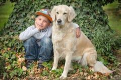 有一只金毛猎犬的小男孩 免版税库存照片