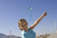 有一只风筝的女孩在风车农场 免版税库存图片