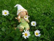 有一只鸟的小矮小的女孩在她的手上坐一个绿色草甸 免版税库存照片