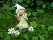 有一只鸟的小矮小的女孩在她的手上坐一个绿色草甸 库存图片